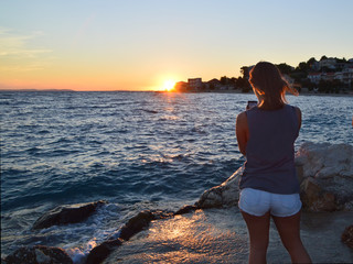 Teenager girl on the beach takes photo of the sunset with her phone