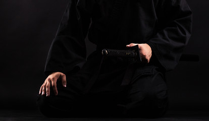 Close up of young martial arts fighter with katana siting in seiza position