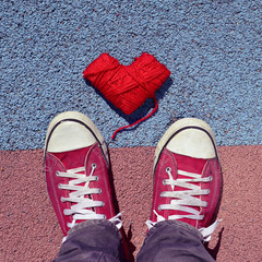 man in sneakers and heart-shaped coil of yarn on the asphalt