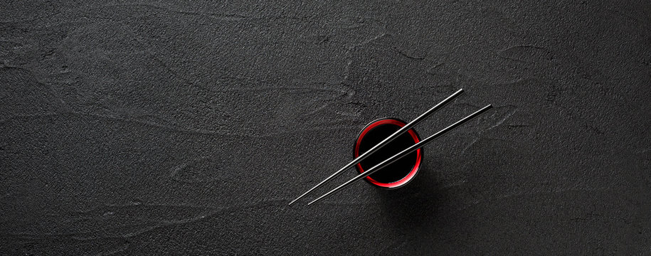 Chopsticks and bowl with soy sauce on black stone background