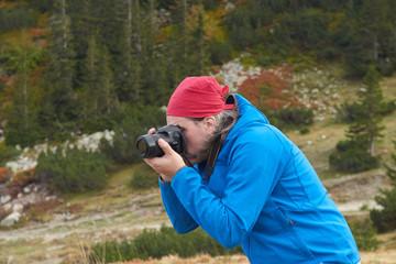 hiking man in nature taking photo