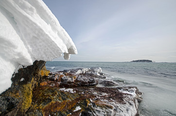 Rocky Maine Coast in Winter - Snow Heave Hanging Over Rock Beach with Icy Ocean Water