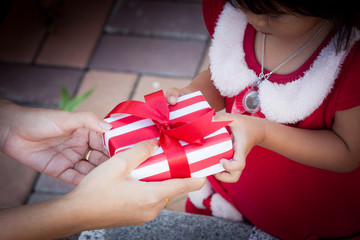 Child cute little girl receiving christmas present from woman