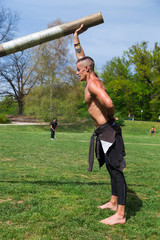 Young athlete man climbing the rope tied to metal construction as part of crossfit training.
