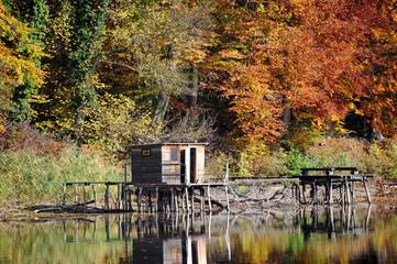 Herbst an einem See mit Fischerhütten