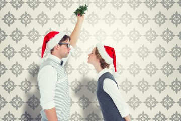 Composite image of geeky hipster kissing under mistletoe