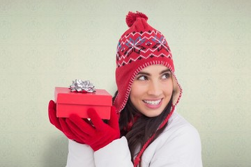 Composite image of happy brown hair holding red gift