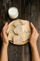 Whole wheat bread on wooden plate hold by hand and milk on wooden background