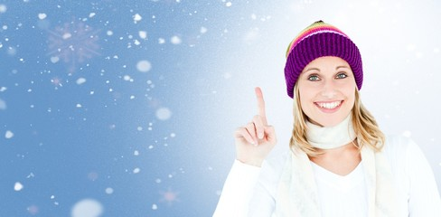 Composite image of joyful woman with a colorful hat pointing up