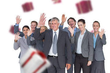 Composite image of smiling business team waving at camera