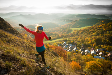 woman with blond hair running on sunlit mountains with view in the early morning