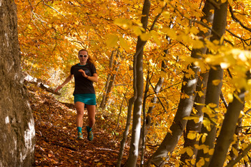 young woman in skirt running fast in the autumn forest with rock