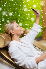 woman taking selfie with smartphone  at spa