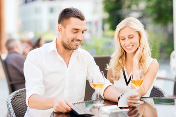 happy couple with wallet and bill at restaurant