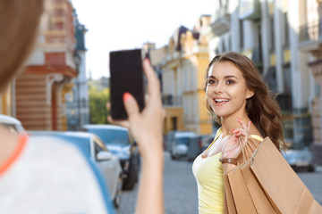 Two young girls taking pictures while shopping