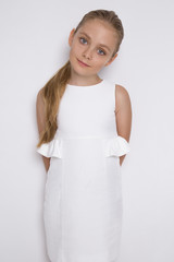 Portrait of a lovely little girl daughter in long blond hair and white dress looks at the camera, photo on the white background amazing eyes
