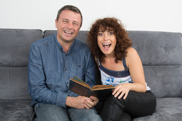 Happy couple reading book and laughing having fun