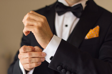 elegant young fashion man looking at his cufflinks while fixing
