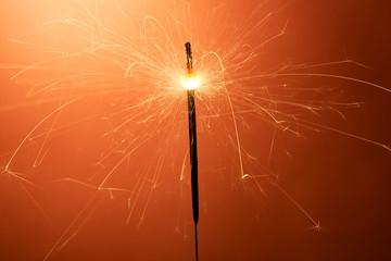 Burning sparkler on an orange background