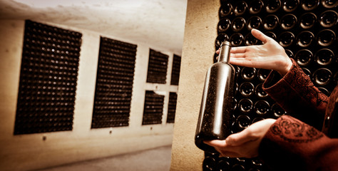 A women holds a bottle of wine in an aging cellar.