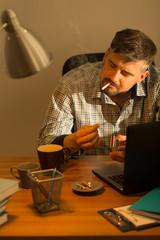 Smoking man at untidy desk