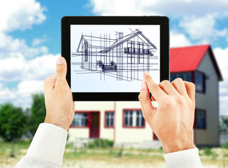 Architect showing new house project on tablet-pc, close up