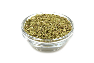 crushed oregano leaves in a glass container on a white background