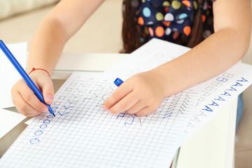 Cute little girl doing her homework, close-up
