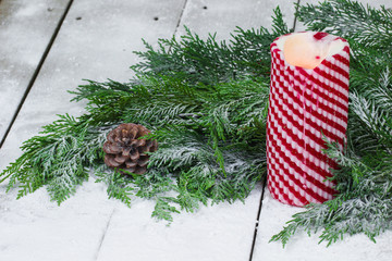 Holiday candle by garland with winter background