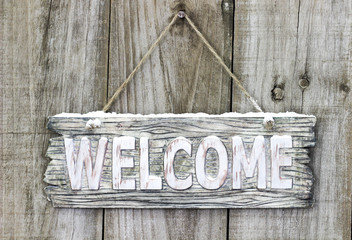 Rustic wood welcome sign with snow hanging on door
