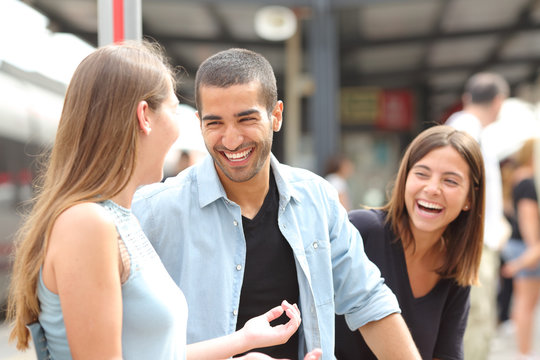 Three friends talking and laughing in a train station
