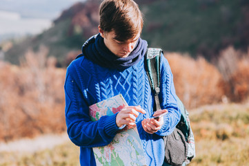 fellow tourist with map in hand and phone. autumn mountains