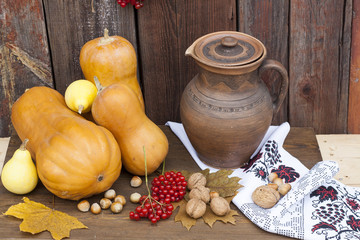 Autumn still life with pumpkins and autumn berry and vegetables on old wooden background, closeup