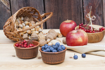 Autumn still life with walnuts and hazelnuts in the basket and autumn berry and vegetables on old wooden background, closeup