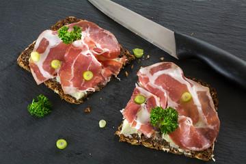 Dark bread with Italian coppa or capicola ham on a dark slate pl