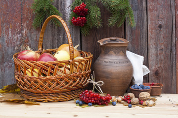 Autumn still life with pumpkins in basket and autumn berry on old wooden background, closeup