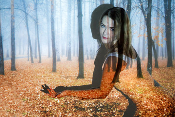 Young woman covered with the picture of the autumn forest