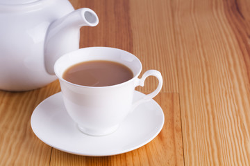 Cup of traditional English Tea with white china teapot