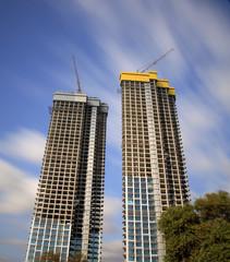 High-rise building under construction against long exposure clou