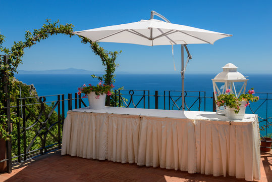 Mediterranean seascape with a table and sun-shade.