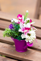 Artificial flowers in colorful metallic vase.
