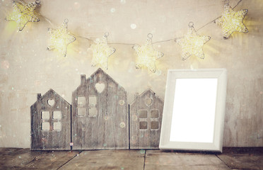 low key image of vintage wooden house decor, blank frame on wooden table and stars garland. retro filtered with glitter overlay. selective focus