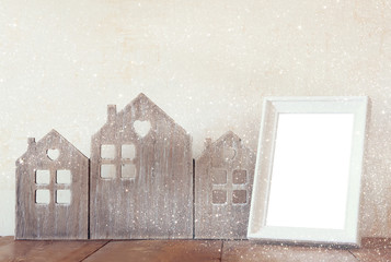 image of vintage wooden house decor, blank frame on wooden table and stars garland. selective focus. with glitter overlay