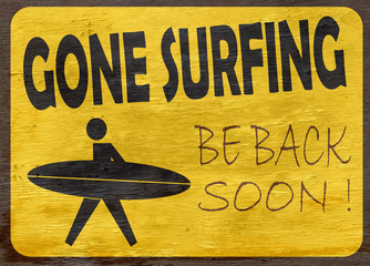 gone surfing sign on wood grain texture