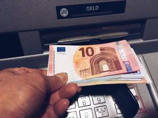 Mann nimmt Geldscheine aus Bank Automat