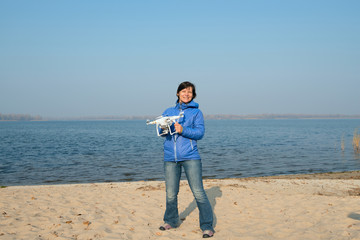 Joyful woman holding a quadcopter, drone and enjoying life on th