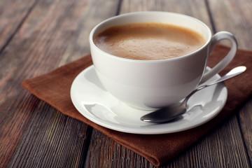 Cup of coffee on brown napkin closeup
