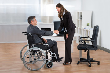 Businesswoman Shaking Hands With Businessman On Wheelchair