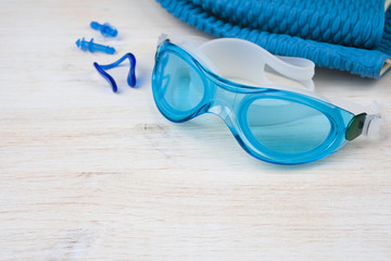 Blue swimming equipment on wooden background. Sport concept