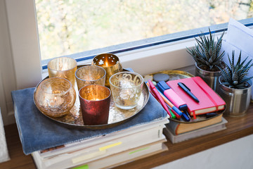 Books, candles, plants and writing instruments on a windowsill. Selective focus on red candle.